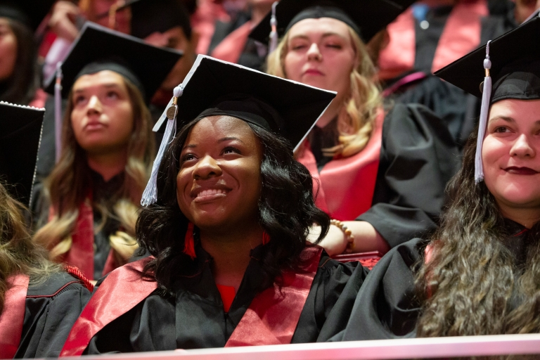 An IU graduate wearing a cap and gown smiles during commencement