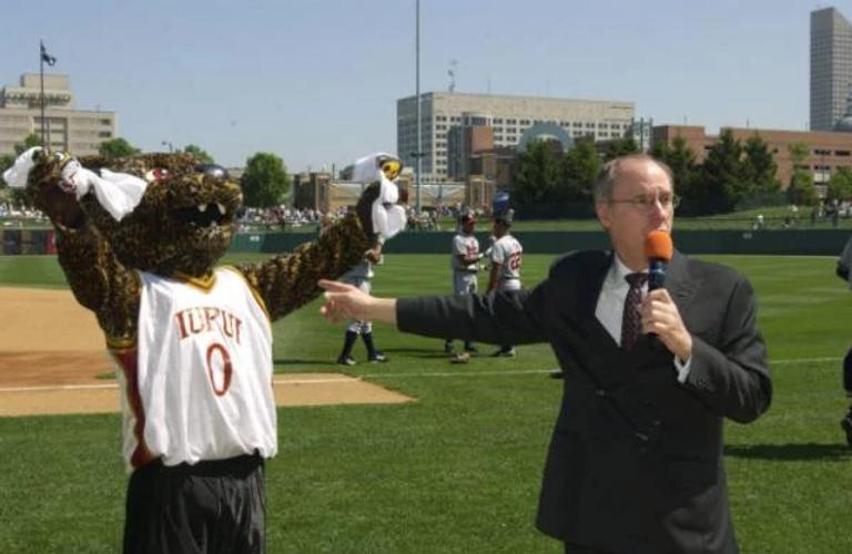 Former chancellor Charles Bantz standing next to a costumed Jaguar mascot at a baseball game