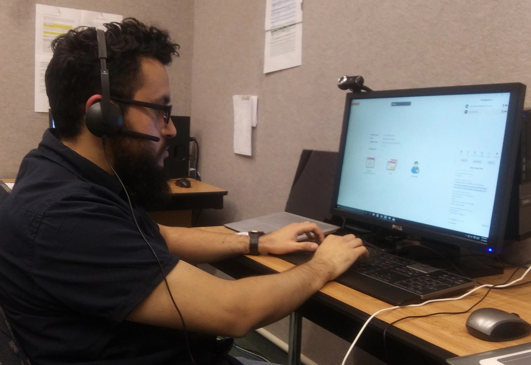 a student with a headset sits at a computer for virtual tutoring and mentoring