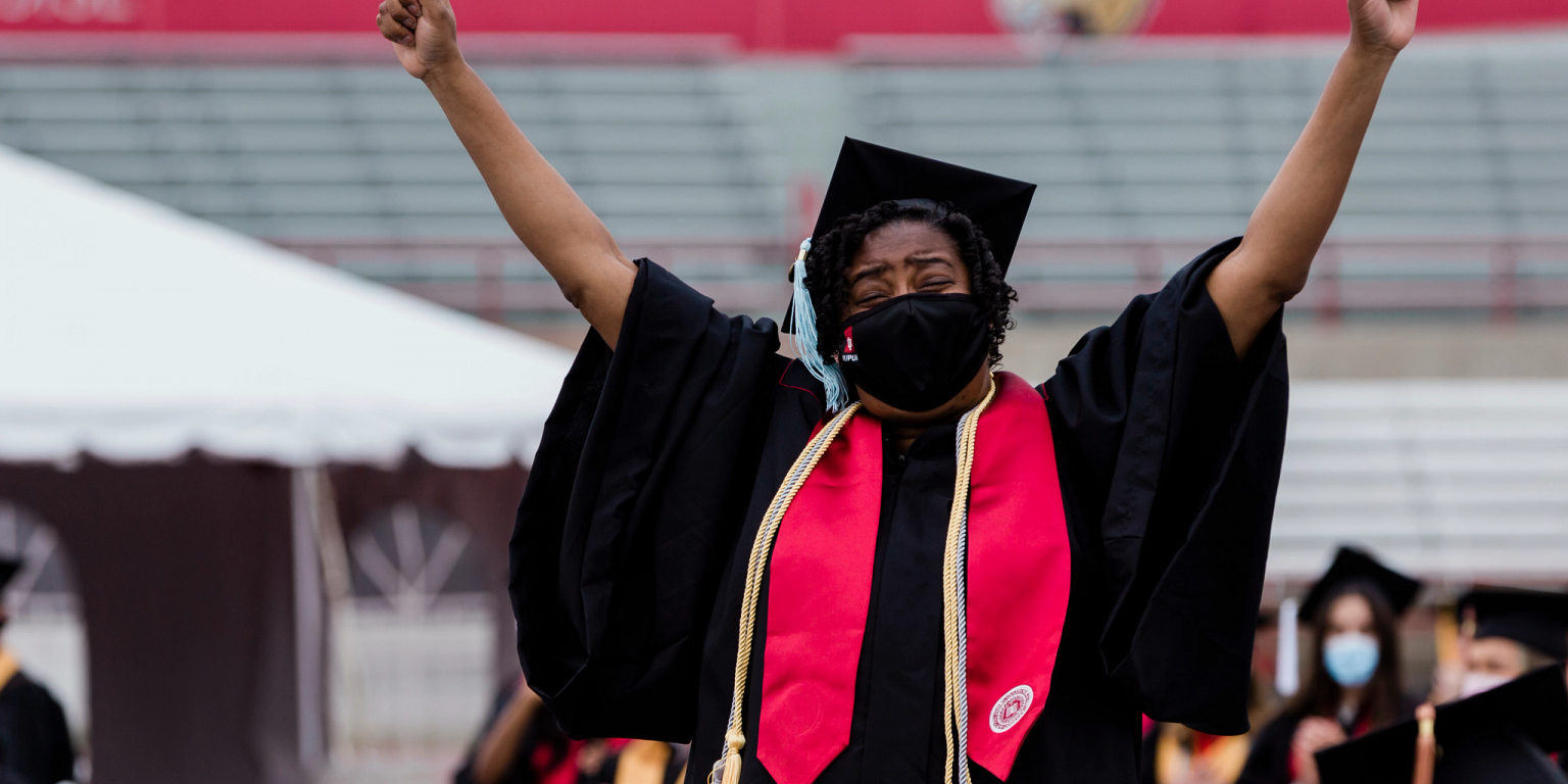 A graduate holds her arms up in celebration