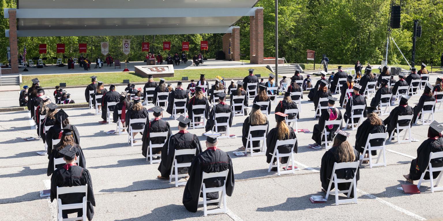 Graduates sit in white folding chairs facing Caesar's amphitheater