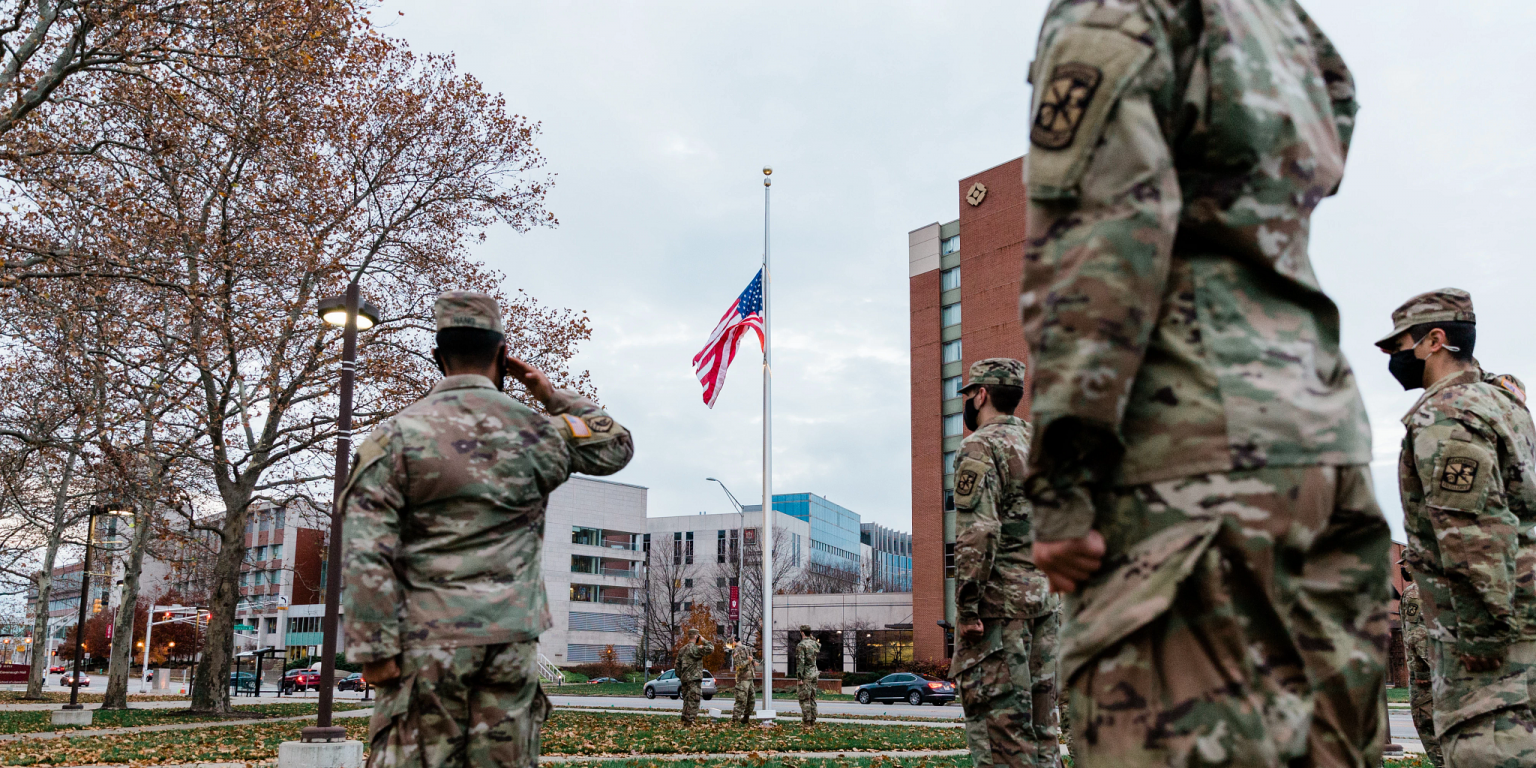 a group of soldiers salute the raising of the American flag