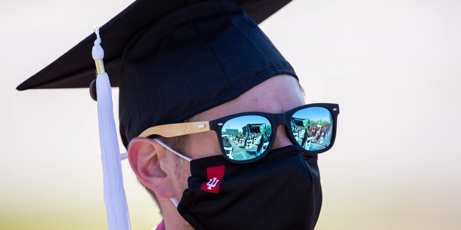 The IU East commencement stage is reflected in a graduate's sunglasses
