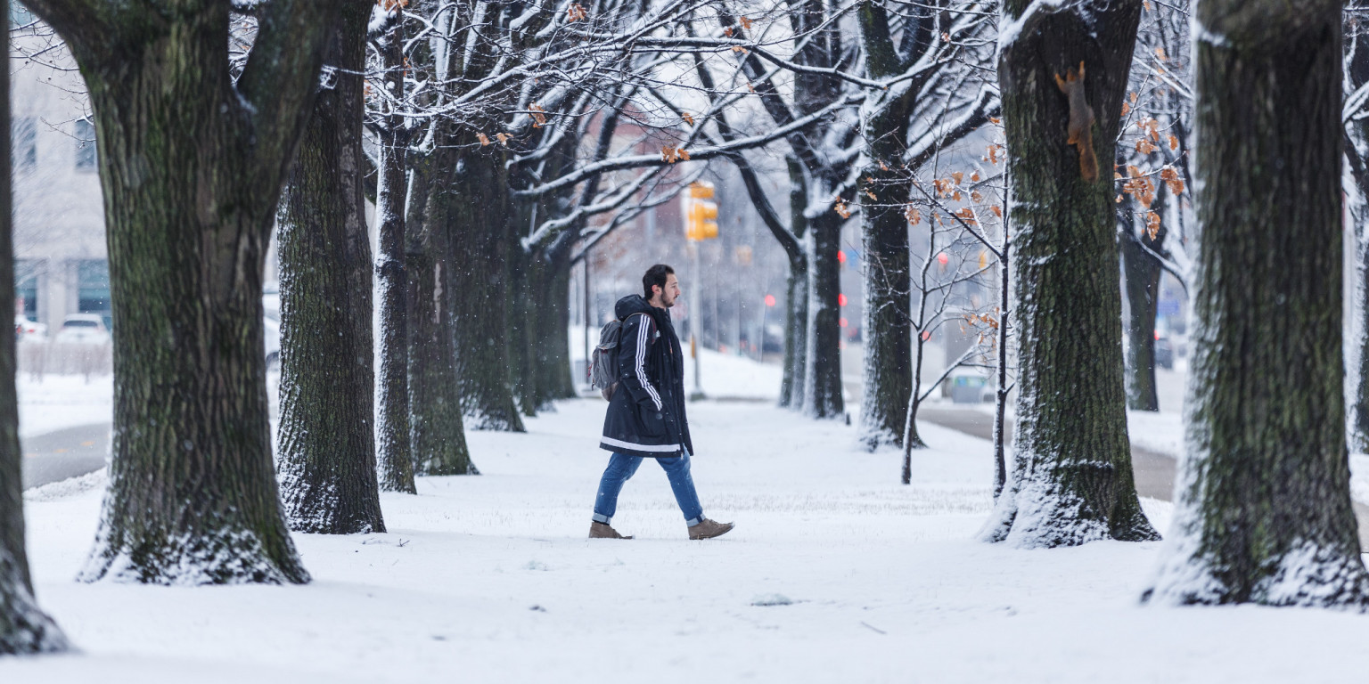 A student walks on campus in the snow