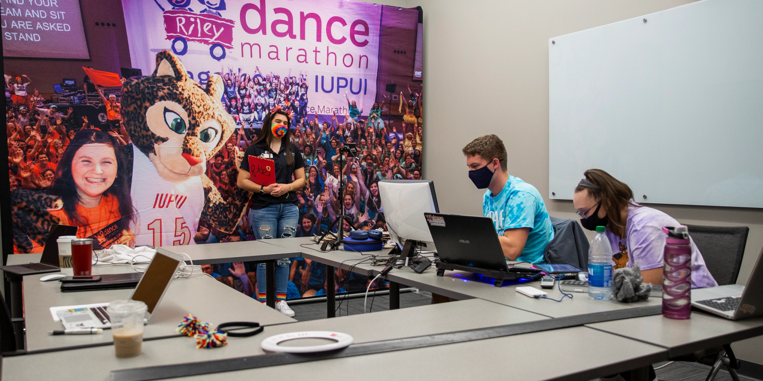 Two students sit around table with laptops and one student stands in front of a Jagathon banner.
