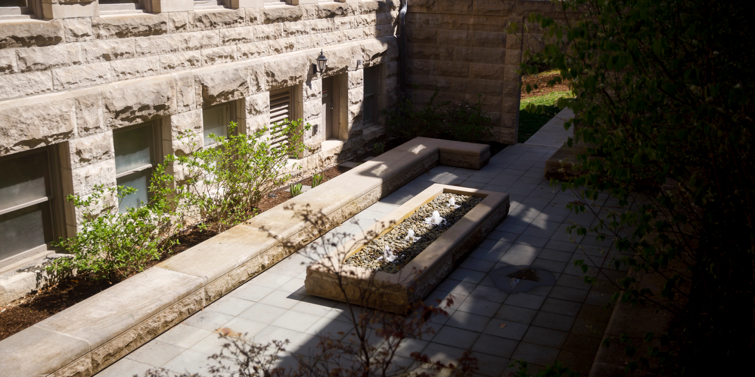 An outdoor courtyard with a fountain in the middle and limestone seating all around