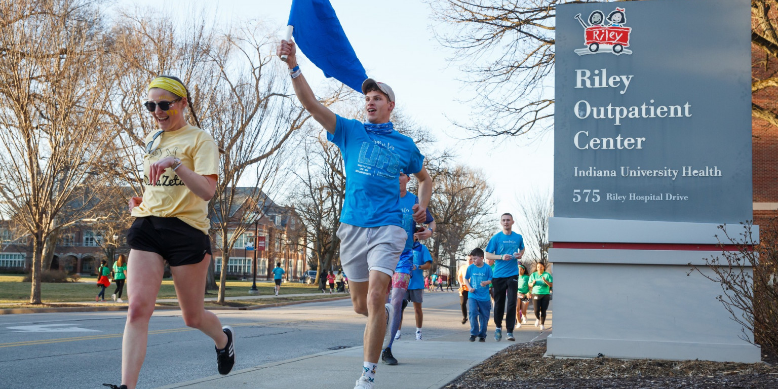 IUPUI students run down the sidewalk past the Riley Outpatient Center in team T-shirts