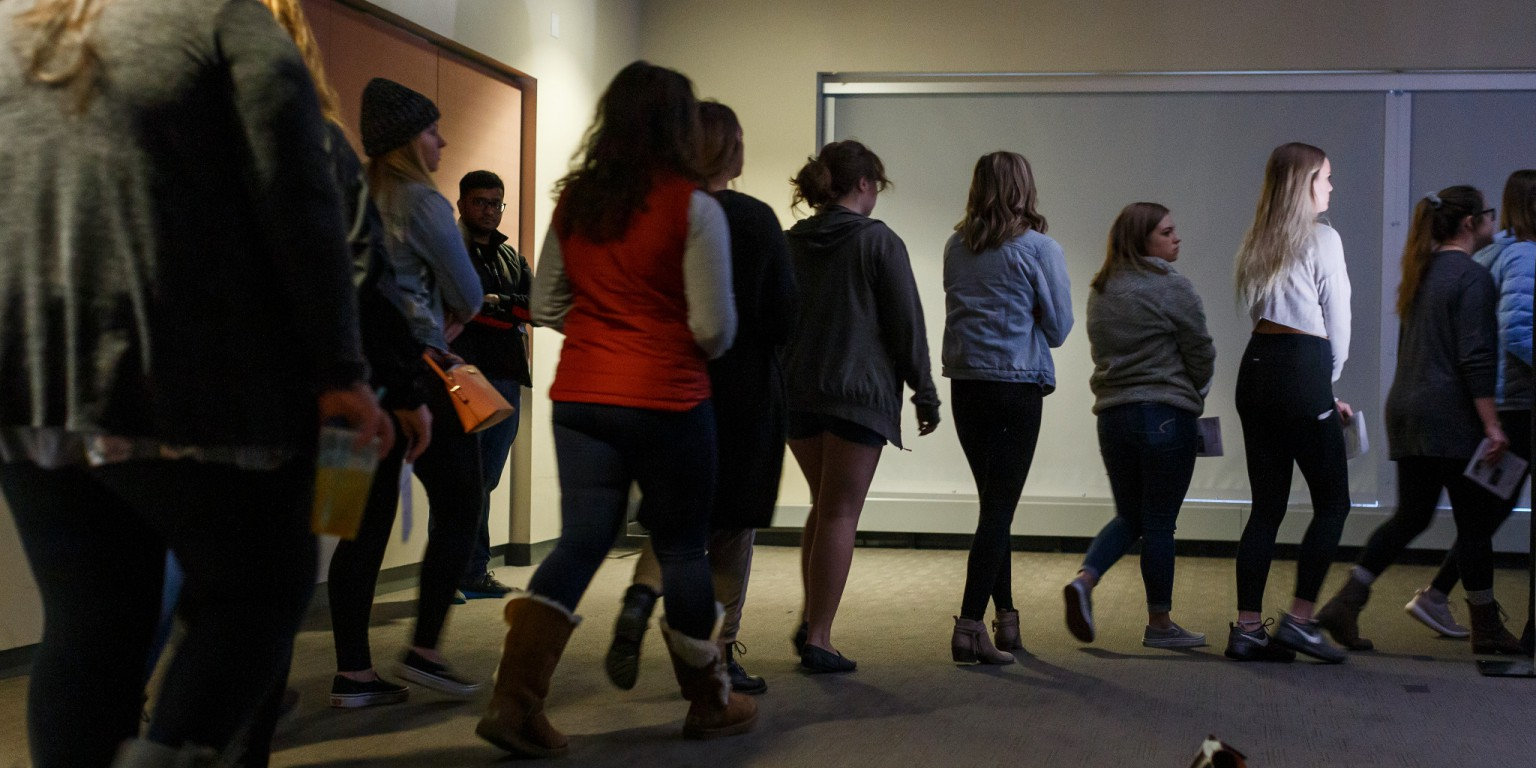 Participants walk in a line through the Tunnel of Oppression from activity to activity.