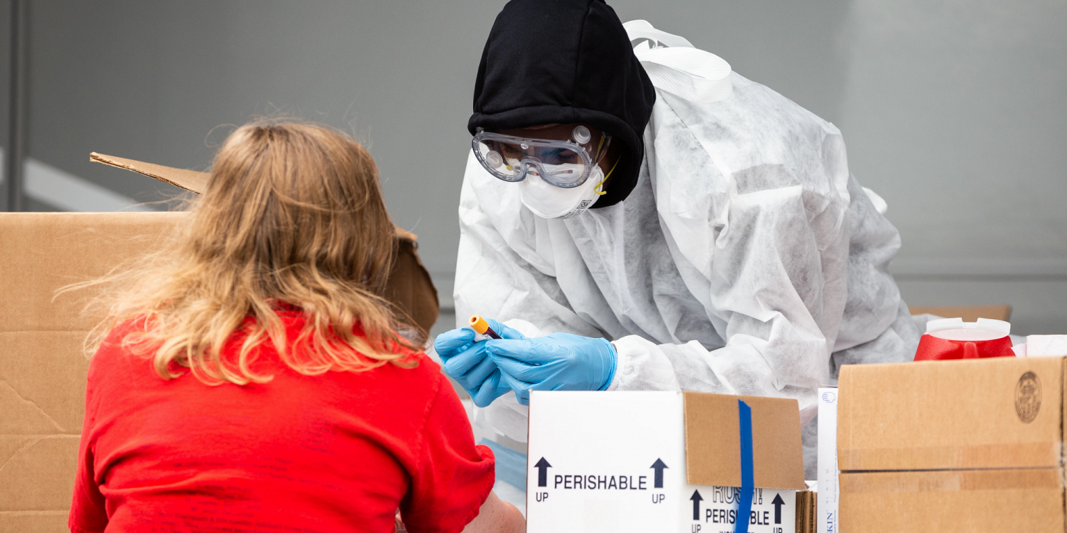 A woman is tested for the novel coronavirus by a worker wearing PPE