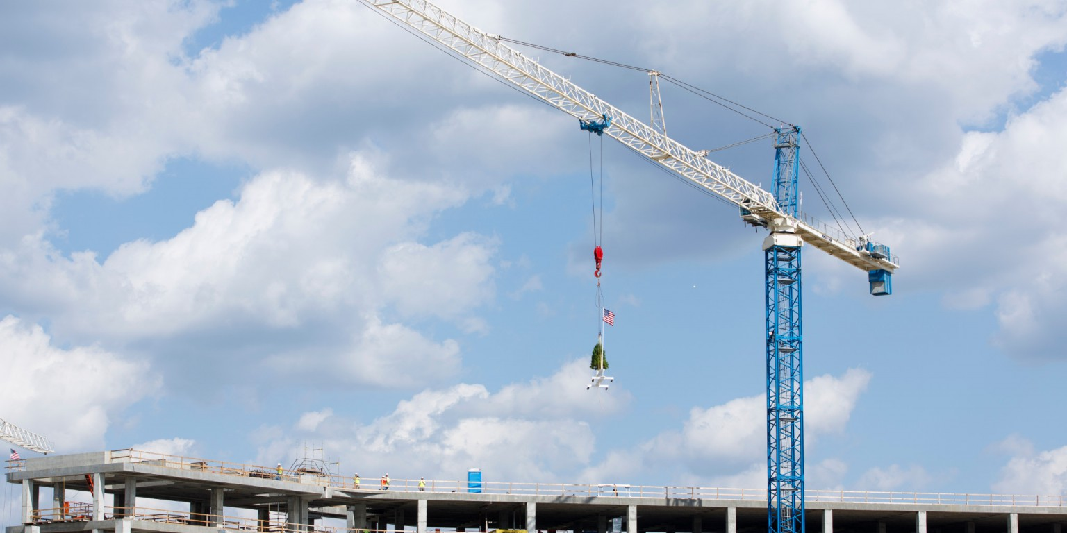 A crane lifts the final beam into place on top of the building