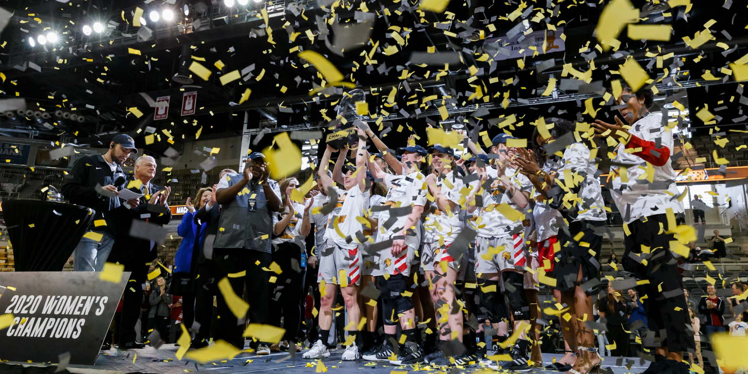 women's basketball team stands on podium with confetti falling