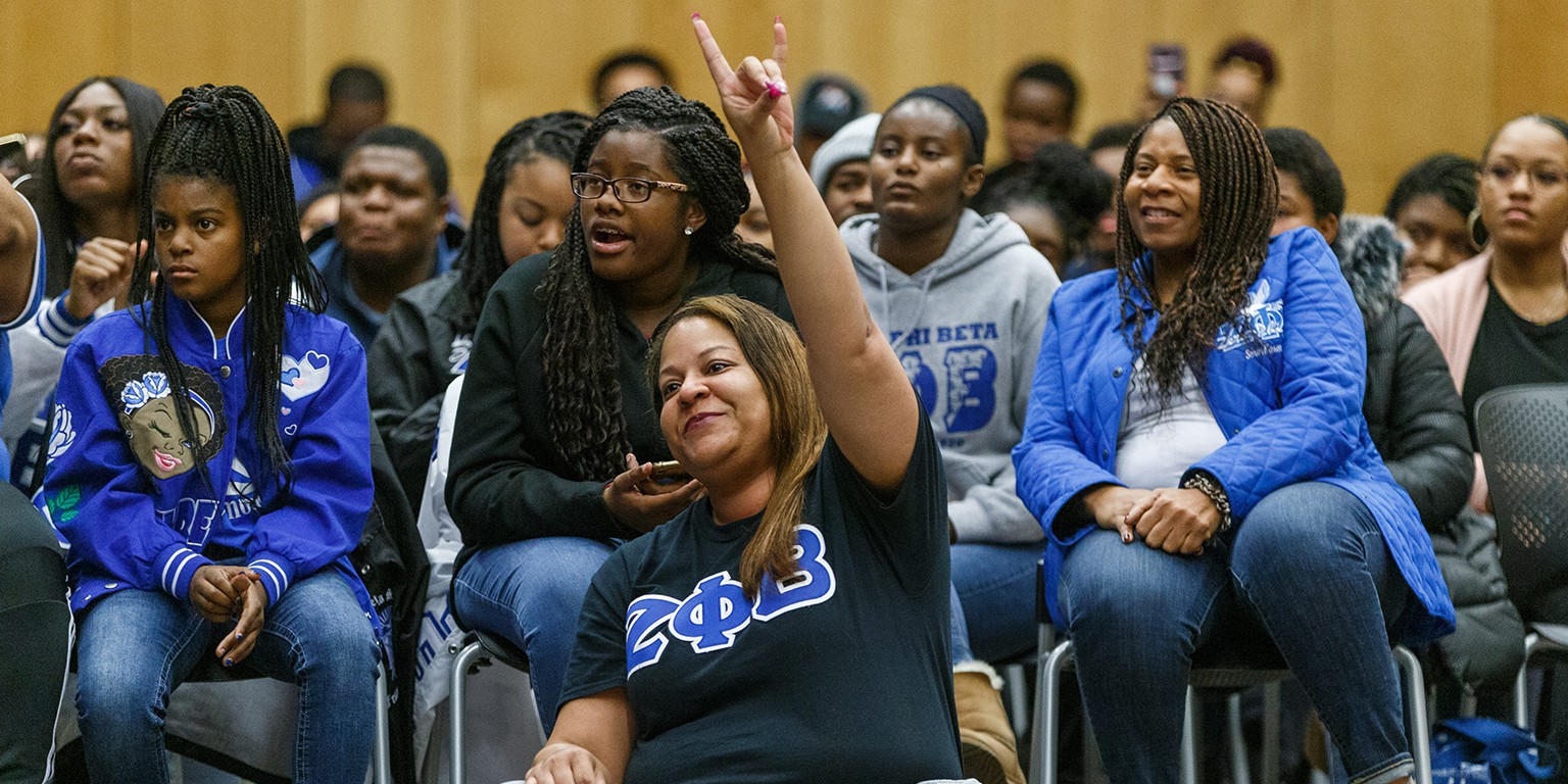 A woman sits in the crowd holding up the hand sign for her sorority, Zeta Phi Beta Sorority