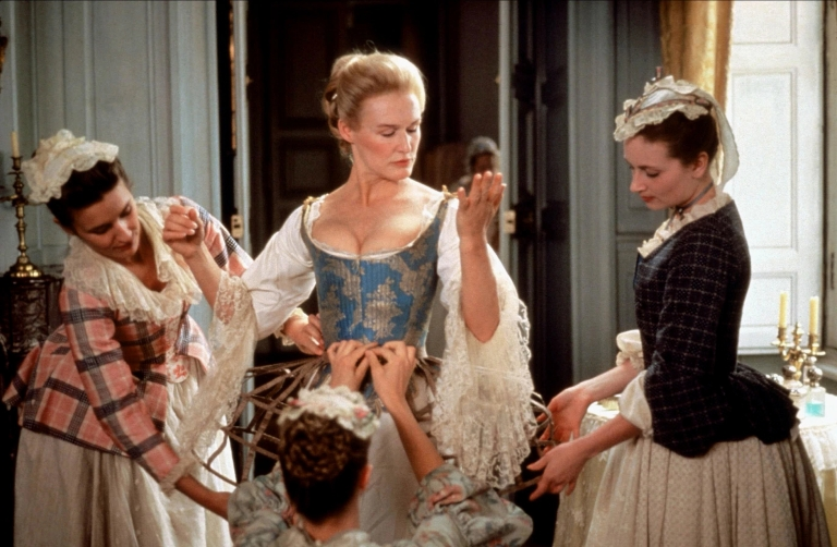 Glenn Close in a Victorian dress surrounded by helpers in a scene from 'Dangerous Liaisons'