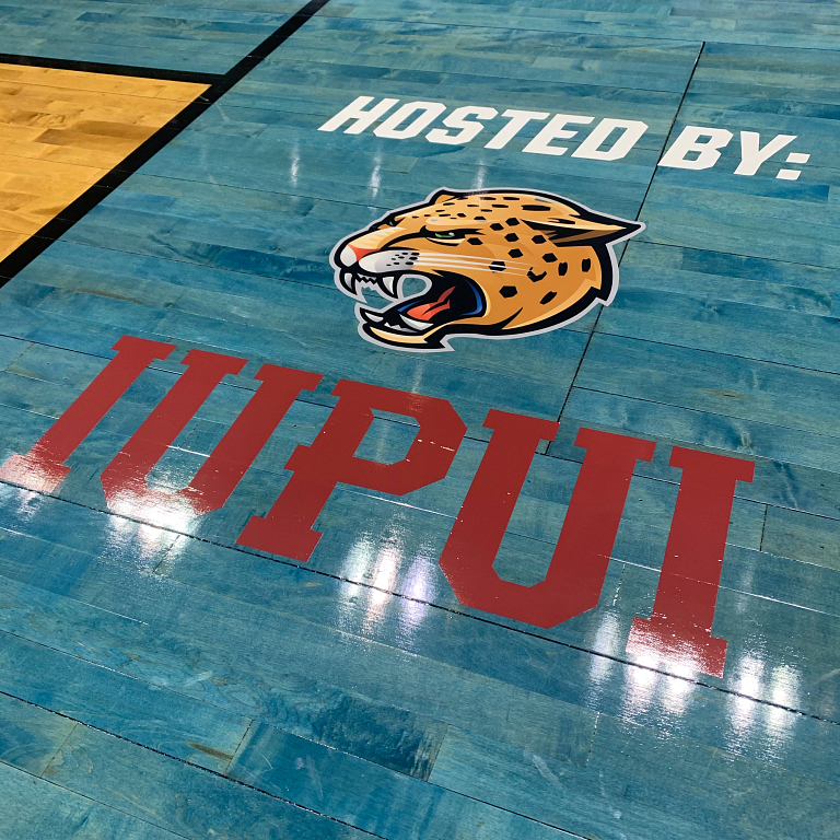 A Jaguars logo with 'Hosted by IUPUI' painted on the basketball court