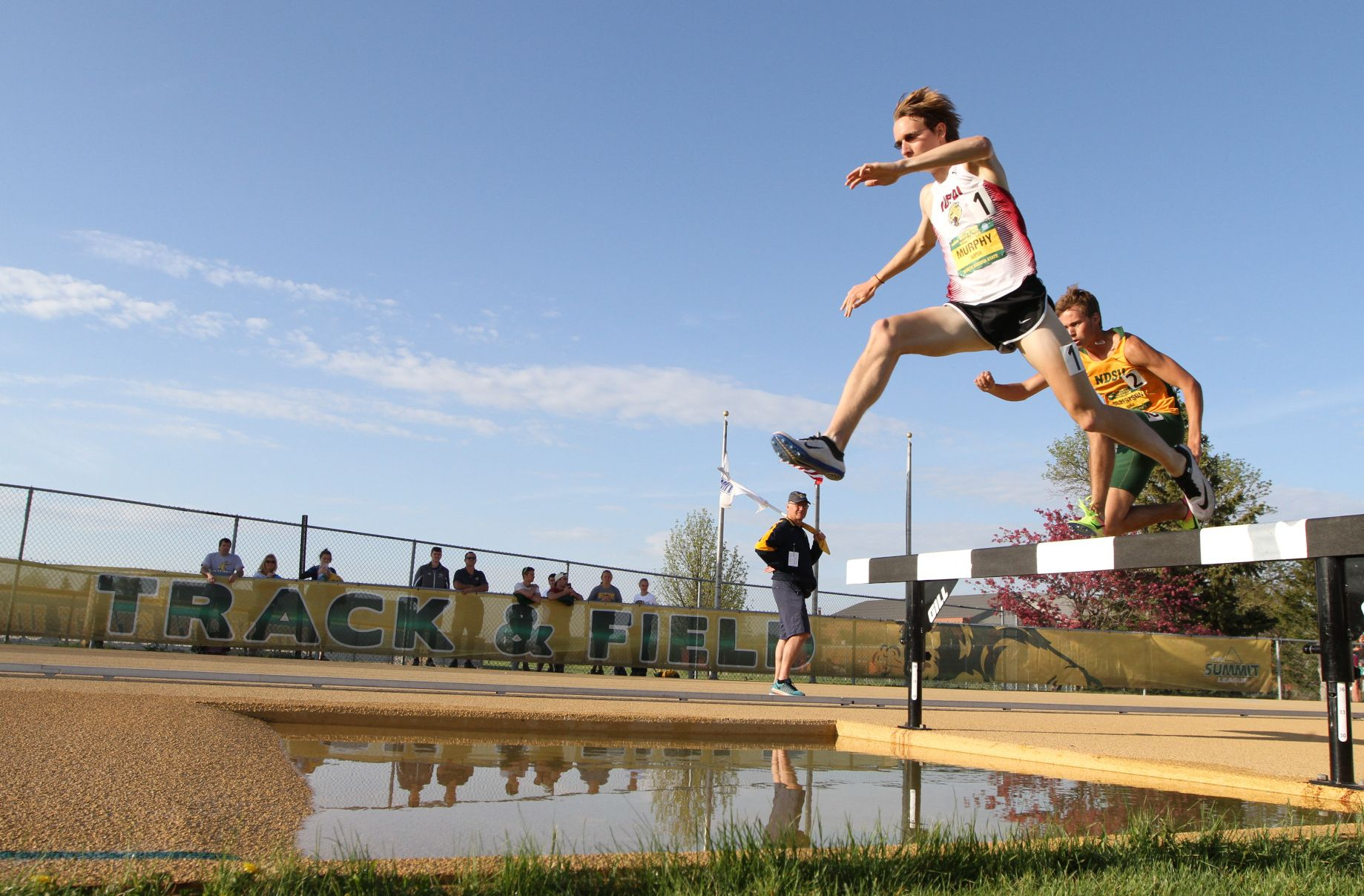 Running for IUPUI, Robert Murphy hurdles a water jump in the steeplechase.