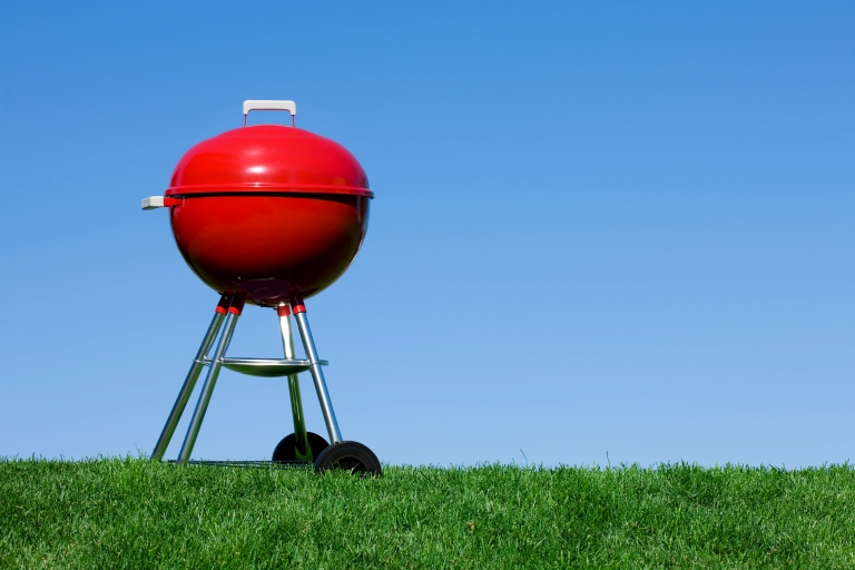 A red grill on a grassy lawn