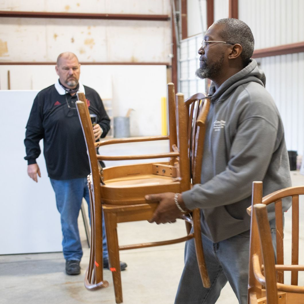 A mover carries two stacked wooden chairs