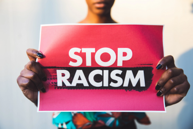 "A Black woman holds a red sign with white lettering that says ""Stop racism"""