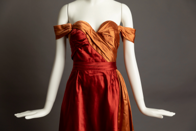 """A closeup of a copper-colored dress from """"Reversal of Fortune"""" displayed on a mannequin"""