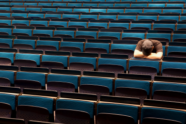 A student sits in an auditorium with his head on his knees.