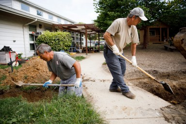 Two landscape services staff members dig on campus
