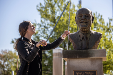 Sonja Rogers uses a tape measure to record the height of a bust of Bill Armstrong.