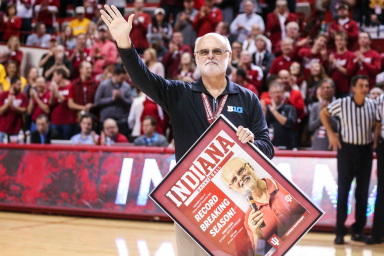 Chuck Crabb waves to a crowd as he holds a framed poster of himself