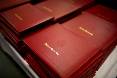 A stack of Indiana University degree folders