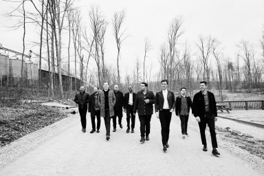Straight No Chaser members walks shoulder-to-shoulder on a gravel path