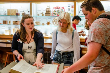 A librarian showcases items from the Lilly Library collection during a First Thursdays event