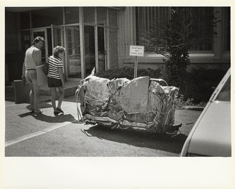 Two people look at a car that's been compacted into a rectangle as it sits in a parking spot