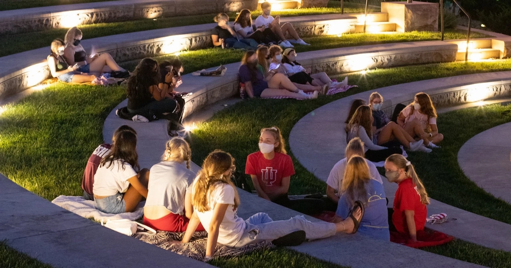 Students wearing face masks sit in small groups at the Conrad Prebys Amphitheater in August 2020.
