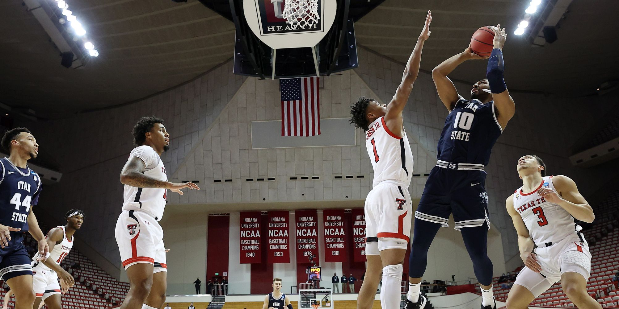 A Utah State player takes a shot over a Texas Tech defender