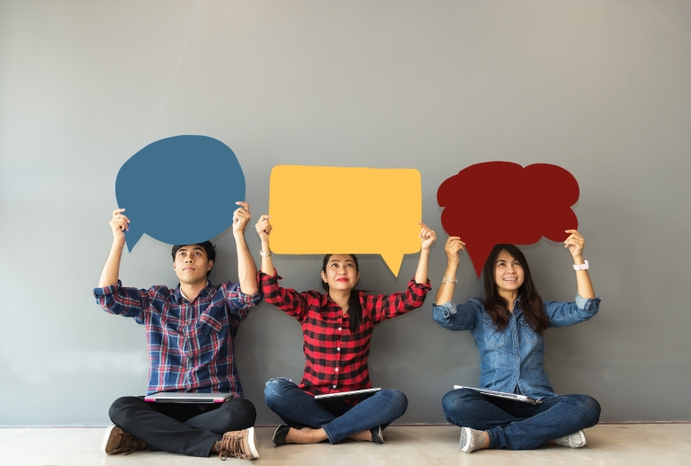 Three people hold up cutouts of thought bubbles over their heads