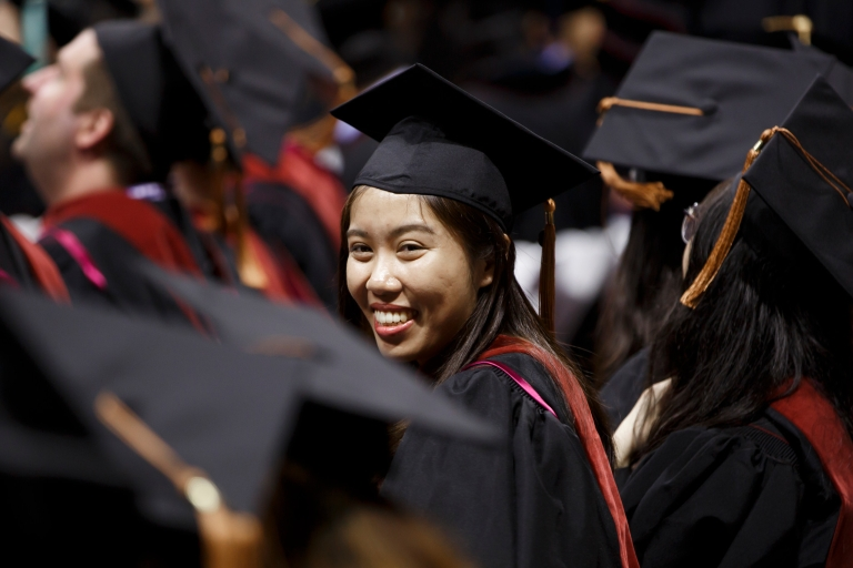 A female students wearing a cap and gown smiles during a commencement ceremony.