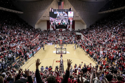 a crowd cheers during a college basketball game