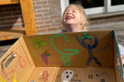 A young girl holds a cardboard box she's painted