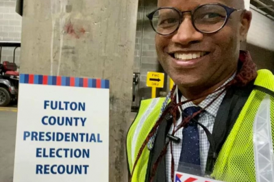 a man stands in front of a sign that says Fulton County Presidential Election Recount