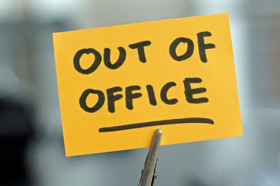 the words 'out of office' on a sticky note