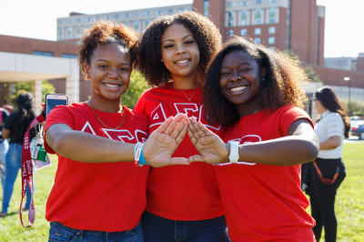 Three women standing close together, making a sorority symbol with their hands