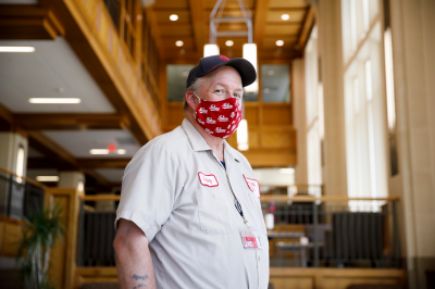A custodian wears a face mask inside a campus building