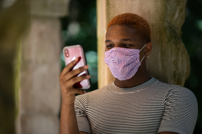 A person wears a mask while holding a cellphone