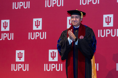 Chancellor Nasser H. Paydar wearing a cap and gown standing in front of an IUPUI backdrop
