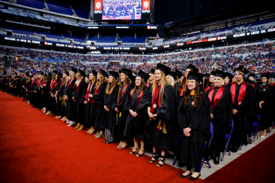 Graduates stand at Lucas Oil Stadium during an IUPUI commencement ceremony