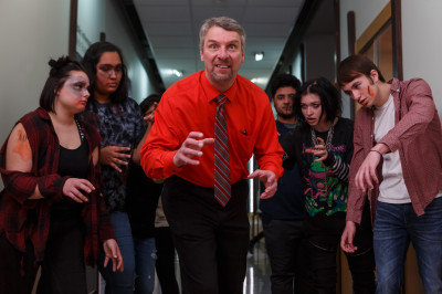 A professor is surrounded by students dressed as zombies