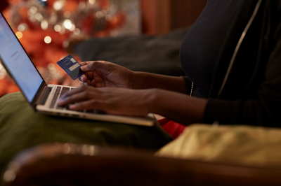 A person shops online using a laptop and credit card