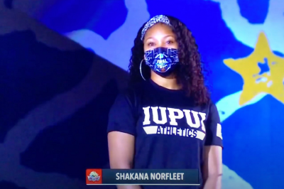 Shakana Norfleet wearing a face mask and preparing to sing the national anthem live on CBS