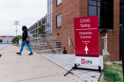 "a red sign that reads ""COVID testing"" with an arrow pointing to a parking garage"