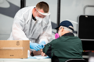 A man in a lab coat taking a sample from a man's arm