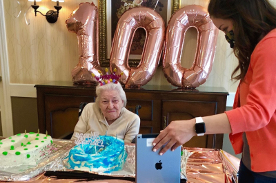 Autumn Hills resident Marjorie Woods celebrates her 100th birthday with friends and family via Zoom with assistance from the UITS iPad.